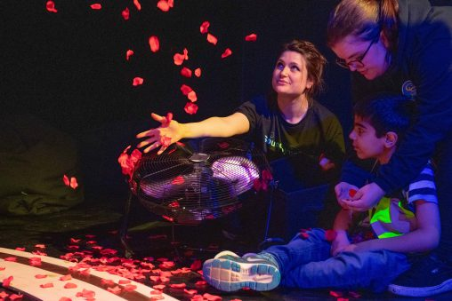 Ellie Griffiths, a young person and carer pictured in Sound Symphony performance, Ellie is sat centre with her arm extended. A large fan pointing upwards and there are rose petals moving, dancing above it.