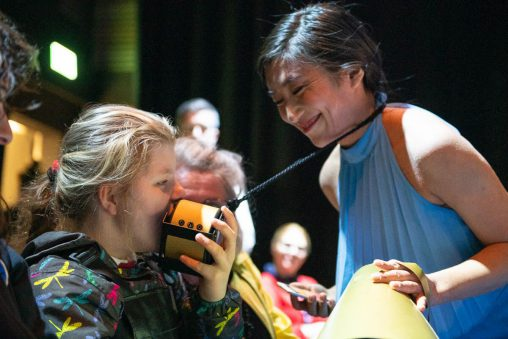 Image from Sound Symphony by Ellie Griffiths (a sensory performance featuring a young person pressing a small speaker to their face and performer Shiori Usui)